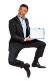 Una tenuta di salto dell'uomo di affari che mostra lavagna Fotografia Stock