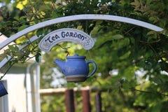 Una tetera azul linda cuelga la entrada a un jardín de té, Irlanda Foto de archivo libre de regalías