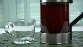 Una tetera de cristal con té preparado fuerte se coloca al lado de la taza almacen de metraje de vídeo