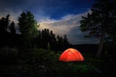 Una tienda brilla intensamente debajo de un cielo nocturno Imágenes de archivo libres de regalías