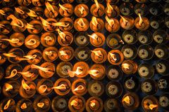 Una tierra de las velas ardientes que se encienden para arriba en el templo budista Imagen de archivo libre de regalías
