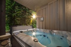 Una tina caliente al aire libre cerca de un bosque con un resplandor solar que viene a través de los árboles imagenes de archivo