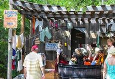 Una tina grande de la lata por completo de agua y mujeres y niños con las muestras divertidas y lavadero que cuelga alrededor en  Fotografía de archivo libre de regalías