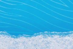 Una tira de nieve natural en fondo de cristal azul del invierno Imagen de archivo