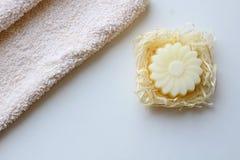 Una toalla beige y un jab?n bajo la forma de flor en un fondo ligero Visi?n superior foto de archivo