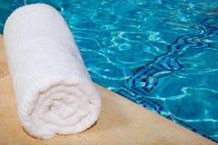 Una toalla blanca enrollada por la piscina azul Imagenes de archivo