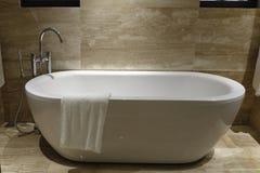 Una toalla colgada en la bañera Fotos de archivo
