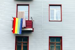 Una toalla colorida cuelga el balcón de OM de la casa gris, a lo largo del concepto de la individualidad, punto brillante en fond foto de archivo libre de regalías