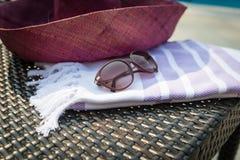 Una toalla turca, gafas de sol y un sombrero de paja blancos y púrpuras en ocioso de la rota con una piscina azul como fondo Fotografía de archivo libre de regalías