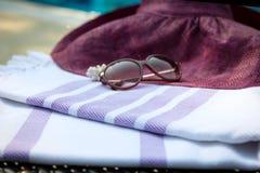Una toalla turca, gafas de sol y un sombrero de paja blancos y púrpuras en ocioso de la rota con una piscina azul como fondo Foto de archivo libre de regalías
