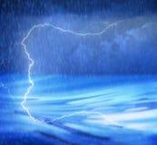Una tormenta de la iluminación en el agua con lluvia y ondas Fotos de archivo
