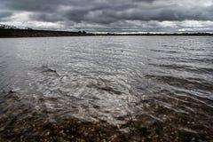 Una tormenta del otoño que elabora cerveza sobre un lago en Staffordshire, Inglaterra Imagenes de archivo