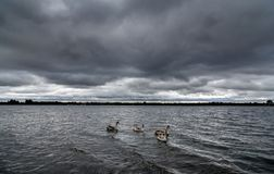 Una tormenta que elabora cerveza sobre un lago en Staffordshire, Inglaterra Foto de archivo libre de regalías