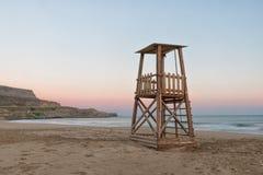 Una torre del bagnino sulla spiaggia mediterranea al tramonto Fotografia Stock