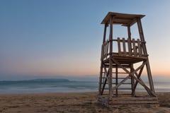 Una torre del bagnino sulla spiaggia mediterranea al tramonto Fotografie Stock Libere da Diritti