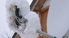 Una torre del plato en el tejado cubierto en nieve Mucha nieve en la antena parabólica almacen de metraje de vídeo