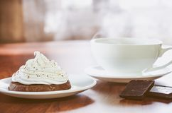 Una torta con crema de la clara de huevo, dos pedazos de chocolate y una taza de café caliente en el fondo en una tabla de madera imagen de archivo libre de regalías