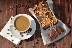 Una torta de chocolate apetitosa adornada con los pequeños pedazos de galletas y colocada envuelto en un papel rústico y una taza Imagen de archivo libre de regalías