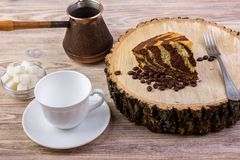 Una torta de chocolate en tocón de madera con una taza de café, una bifurcación, granos de café y un cuenco con los cubos del azú Imagenes de archivo