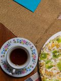 Una torta hecha de las galletas, adornadas con las rebanadas del kiwi, las mentiras en una placa blanca al lado de un platillo y  fotografía de archivo