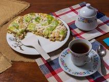 Una torta hecha de las galletas, adornadas con las rebanadas del kiwi, las mentiras en una placa blanca al lado de un platillo y  imagenes de archivo