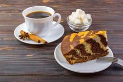 Una torta sabrosa y una taza de café Un intestino con los cubos del azúcar y los palillos de canela en una pequeña placa cerca de Fotografía de archivo