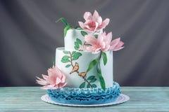 Una torta tres-con gradas de la boda casera hermosa adornada con las flores y las ramas rosadas con las hojas verdes en un estilo Fotos de archivo libres de regalías