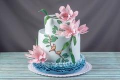 Una torta tres-con gradas de la boda casera hermosa adornada con las flores y las ramas rosadas con las hojas verdes en un estilo Imagen de archivo