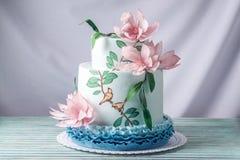 Una torta tres-con gradas de la boda casera hermosa adornada con las flores y las ramas rosadas con las hojas verdes en un estilo Fotografía de archivo