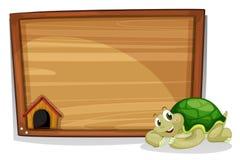 Una tortuga al lado del tablero de madera vacío stock de ilustración