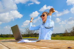 Una trabajadora acertada con un ordenador portátil y los brazos para arriba Fotos de archivo libres de regalías