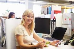 Una trabajadora que come el almuerzo usando el teléfono elegante, teléfono en su escritorio Imágenes de archivo libres de regalías