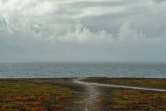 Una traccia del piede che conduce fuori al bordo di una scogliera costiera fotografia stock libera da diritti