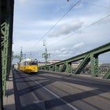 Una tranvía amarilla en el puente verde Fotos de archivo libres de regalías