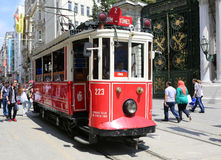 Una tranvía roja histórica delante de la High School secundaria de Galatasaray en el extremo meridional de la avenida istiklal Imágenes de archivo libres de regalías
