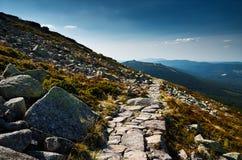 Una trayectoria de la piedra de la montaña Nubes blancas en un cielo azul fotografía de archivo libre de regalías