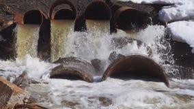 Una trompeta grande, vieja hecha del hierro De ella fluye el agua en el río a veces sucio y dañino almacen de video