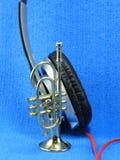 Una trompeta miniatura apoyada para arriba en un negro y un auricular de plata foto de archivo libre de regalías