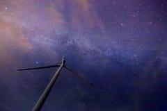 Una turbina de viento con la vía láctea hermosa en fondo con las estrellas brillantes sobre tierra plana a la medianoche foto de archivo
