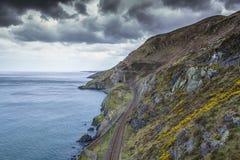 Una vía del tren encendido en el lado de una montaña Fotos de archivo libres de regalías