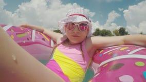 Una vacanza allegra sulla spiaggia, una ragazza nel Panama fresco e gli occhiali da sole d'uso naviga su un cerchio gonfiabile ro video d archivio