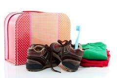 Una valigia con i pattini ed i panni Fotografie Stock