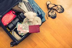 Una valigia con l'orsacchiotto di cose e un passaporto straniero Fatture asiatiche del cento-dollaro e dei soldi per il viaggio C fotografie stock libere da diritti