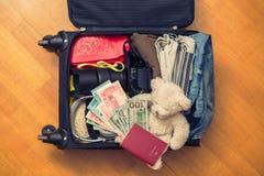 Una valigia con l'orsacchiotto di cose e un passaporto straniero Fatture asiatiche del cento-dollaro e dei soldi per il viaggio C immagini stock