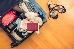 Una valigia con l'orsacchiotto di cose e un passaporto straniero Fatture asiatiche del cento-dollaro e dei soldi per il viaggio C fotografie stock