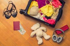 Una valigia con l'orsacchiotto di cose e un passaporto straniero Fatture asiatiche del cento-dollaro e dei soldi per il viaggio C fotografia stock libera da diritti