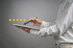 Una valutazione di cinque stelle o posto, concetto di valutazione L'uomo con il PC della compressa valuta il servizio, hotel, ris Fotografia Stock