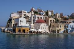 Una variedad colorida de edificios se sienta adyacente a la entrada al puerto de Kastellorizo en Grecia Imagen de archivo libre de regalías
