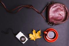 Una variedad de accesorios del ` s de las mujeres bajo la forma de bolsos, tazas de café y la cámara en fondo oscuro Imagen de archivo
