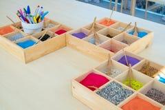 Una variedad de arena del color puso en una pequeña bandeja hecha de la madera usada para enseñar a arte Imágenes de archivo libres de regalías